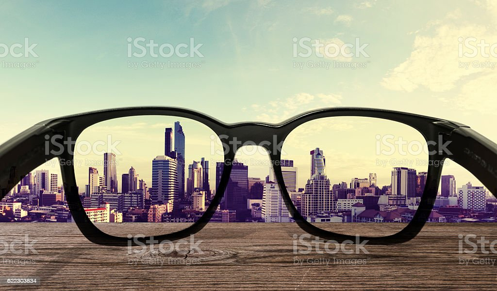 Sunglasses on wooden desk with city view background stock photo