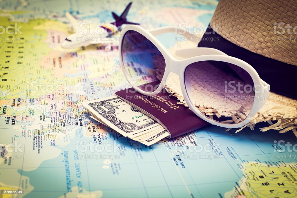 Sunglasses, Passport, Money, Hat and aircraft on the world map - Photo