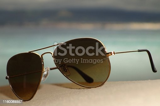 Sunglasses, - aviator style on a sunny day with ocean and blue skies in the background.