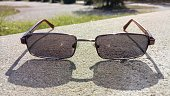 Sunglasses On A Concrete Slab With Shadows