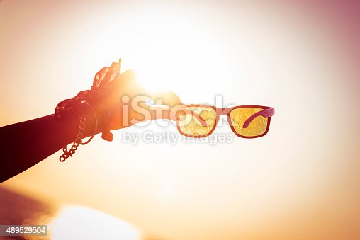 Woman holding sunglasses towards the sun
