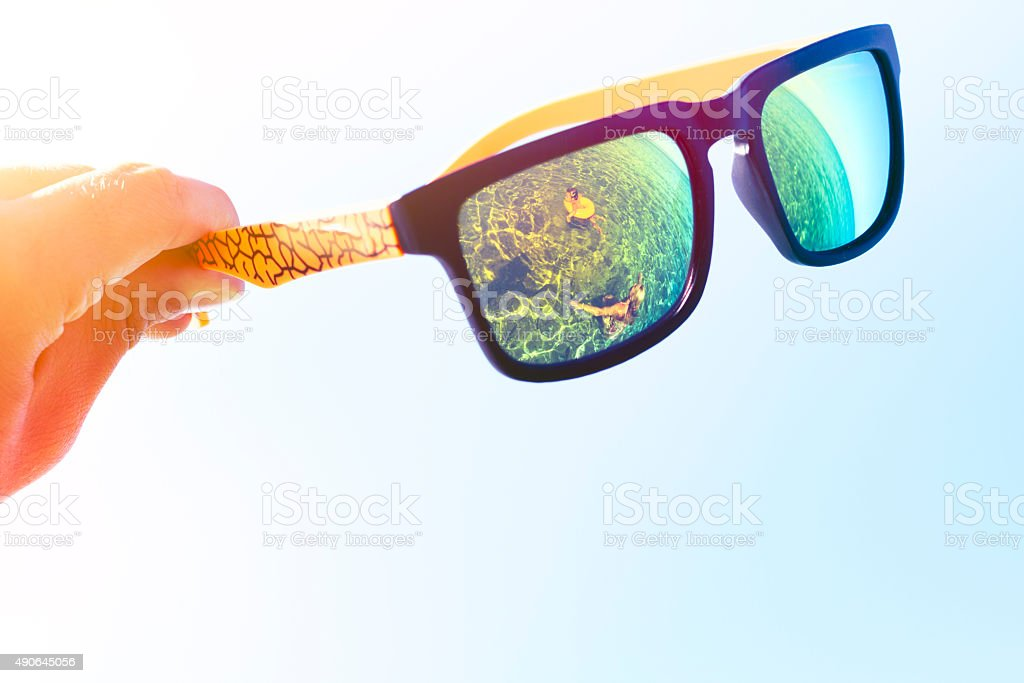 Sunglasses reflecting family swimming in sea stock photo