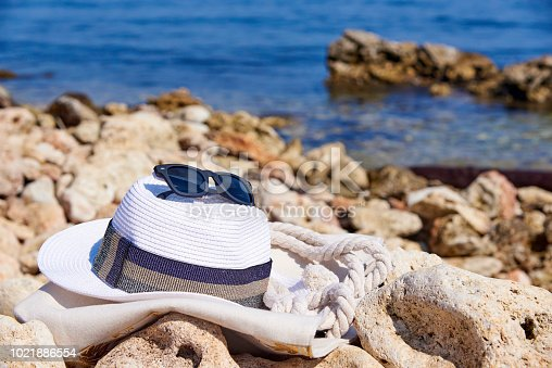 674650538istockphoto Sunglasses with a hat on a stone on the background of the sea 1021886554