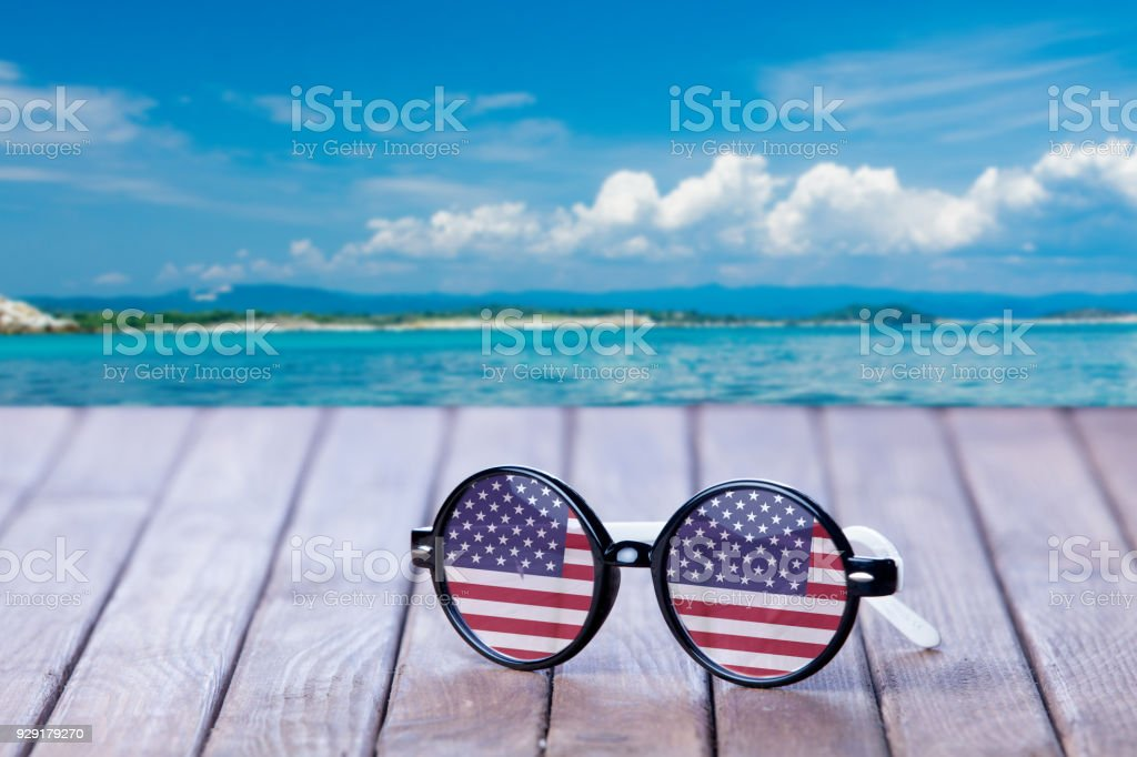 Sunglasses with american flag on wooden table stock photo