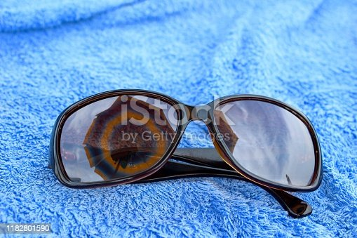 accessory, background, bath, beach, beach umbrella, blue, blue background, bright, close up, closeup, color, concept, conceptual, copy space, design, eye, fashion, glasses, holiday, leisure, lifestyle, minimalism, object, one object, protection, recreation, reflection, relax, scene, style, summer, sun, sun umbrella, sunglasses, sunny, symbol, travel, trip, vacation