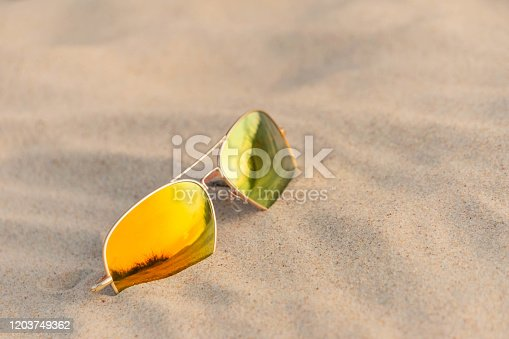 Sunglasses on beach reflecting sand dunes. Mirrored sunglasses on sandy beach in summer day. Sunglasses on sand as summertime vacation concept.