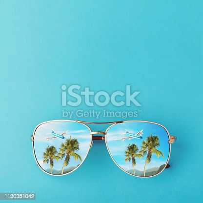 istock Sunglasses with palm trees, a plane and mountains reflected in them. Concept on the theme of vacation and travel with copy space 1130351042