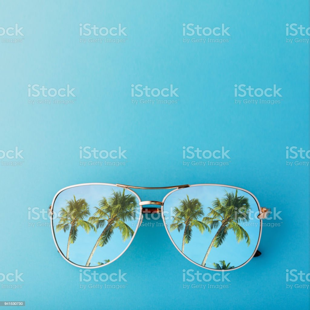 Sunglasses with palm trees reflected in them and space for text, top view stock photo