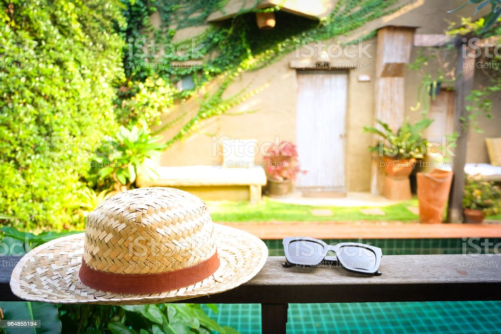 Sunglasses with vintage straw hat fasion on wooden table, Blur background for vintage resort hotel, Concept Summer royalty-free stock photo