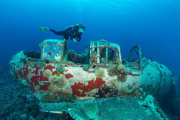 II WW Sunken Airplane Wreck -Palau This navy floatplane, an Aichi E13A1-1 or Jake type reconnaissance seaplane is one of the most intact wrecks in Micronesia, resting at 45 feet (15m). Beautiful scenario of a II WW Japanese seaplane sunken and a female scuba diver in Palau - Micronesia. The Jake could be found in many lagoons where the land mass did not support an airfield, but they also operated from cruisers and battleships. Two of the planes can be seen (in Palau) in very shallow waters in a cave of Babelthuap. sunken stock pictures, royalty-free photos & images