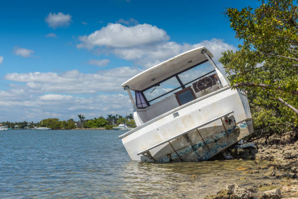Sunken dreams Boat damaged and abandoned by the passage of a cyclone in Miami. sunken stock pictures, royalty-free photos & images