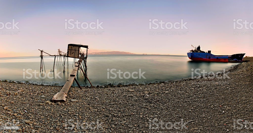 sunken ship and pier long exposure stock photo