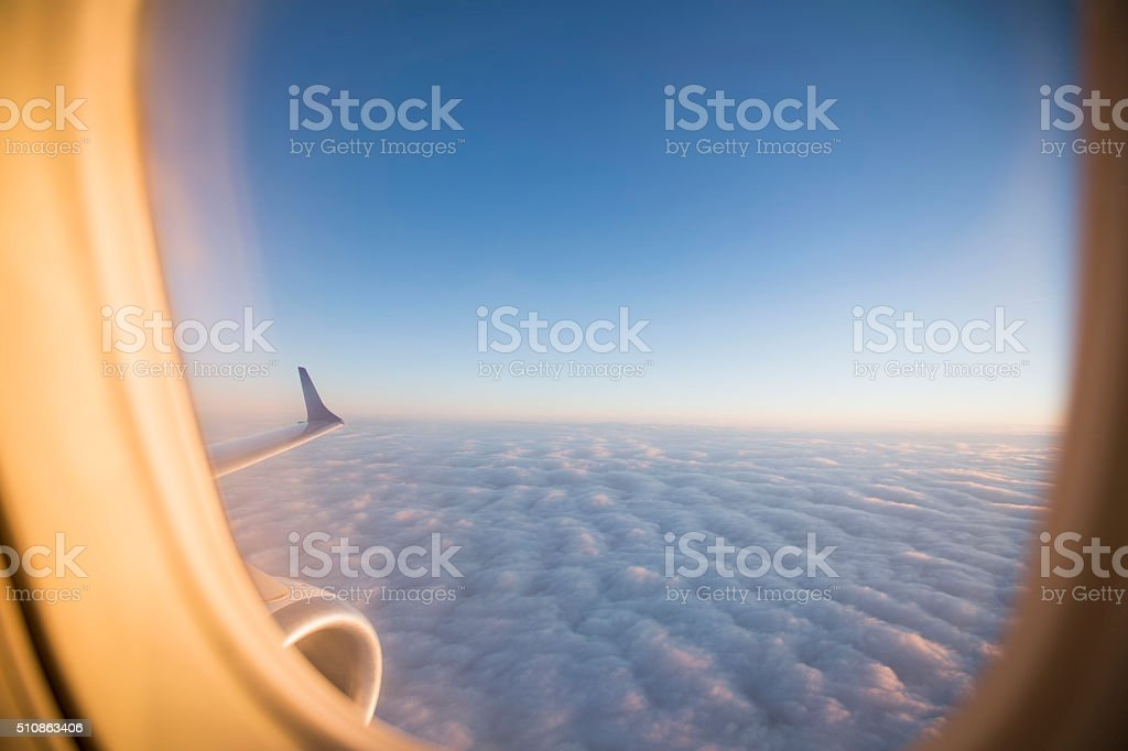 Sunlight and clouds from the porthole on airplane stock photo