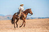 Cowgirl is riding a horse in nature in Utah, USA.
