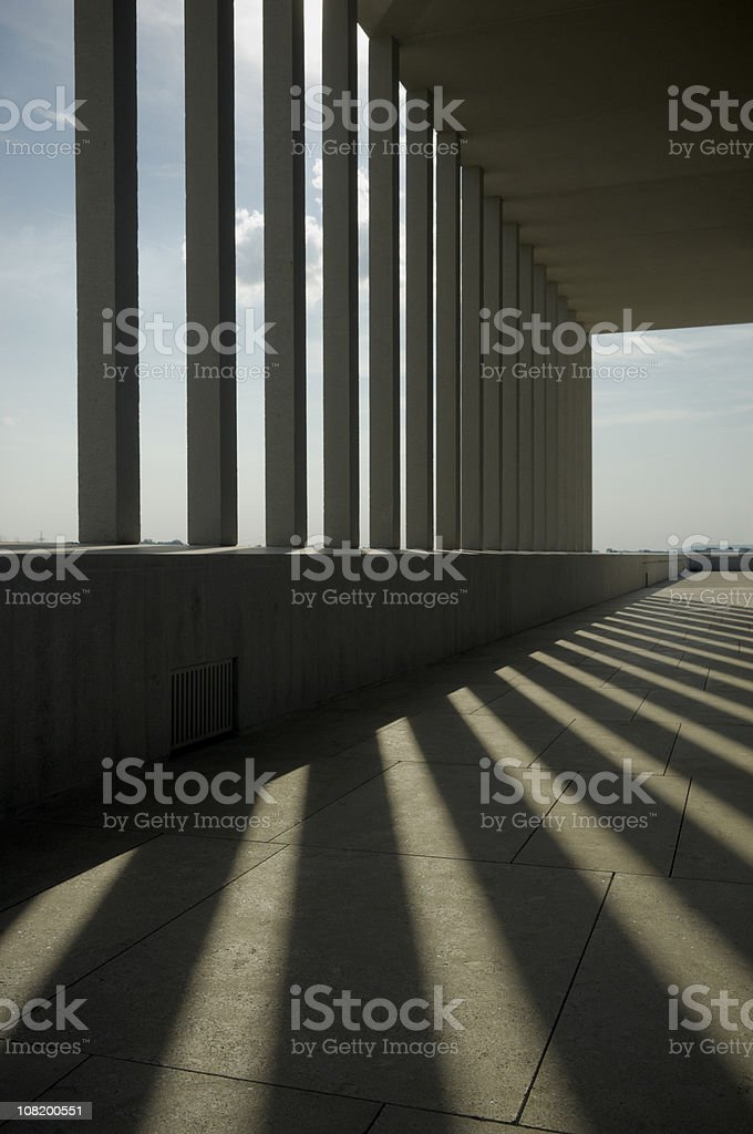 Sunlight and Shadows Through Columns of Building stock photo