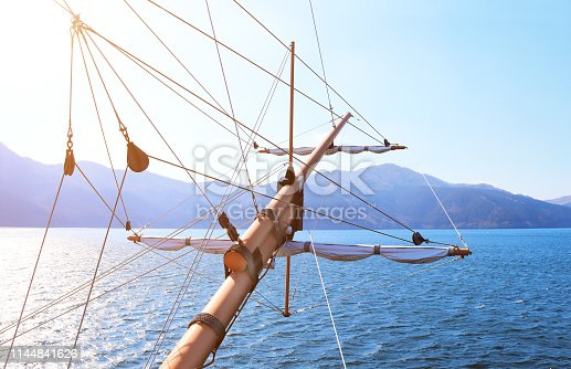 Sunlight at sea on a tall ship classic sailboat. Beautiful landscape with mountains, sea and ship rigging. Cruise on retro ship at lake Ashi, Hakone, Japan