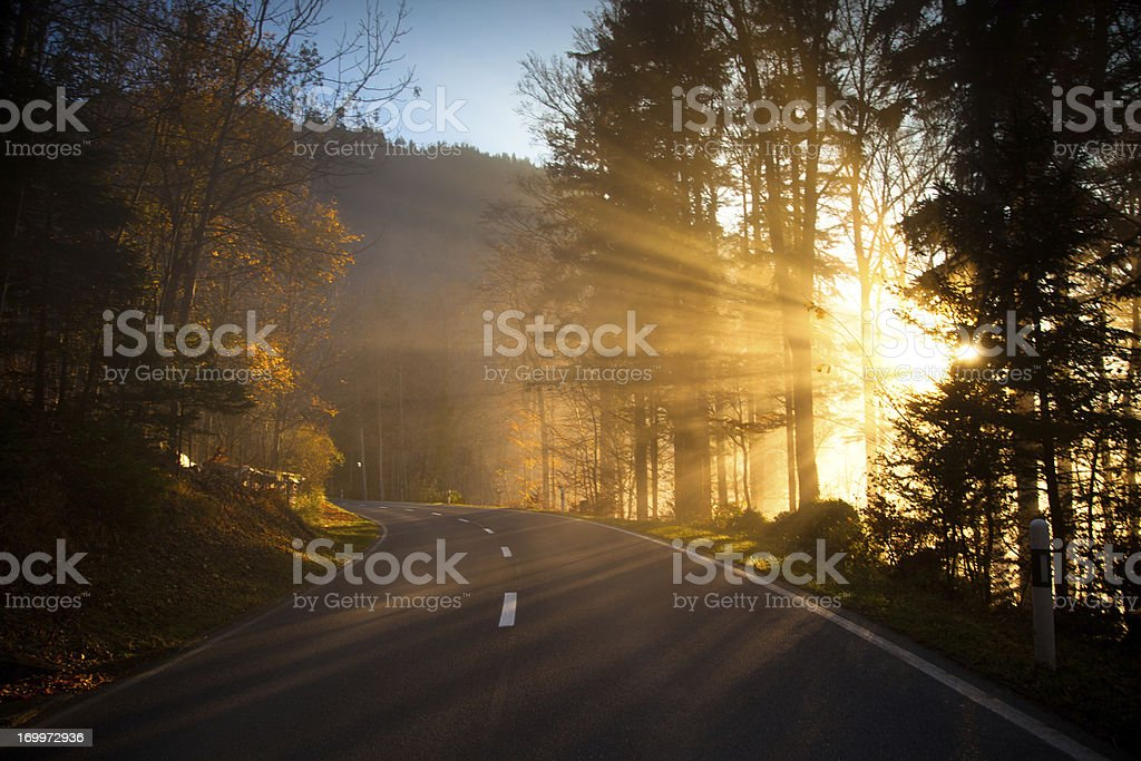 Sunlight Beams Cutting Through Mountain Road, Switzerland stock photo
