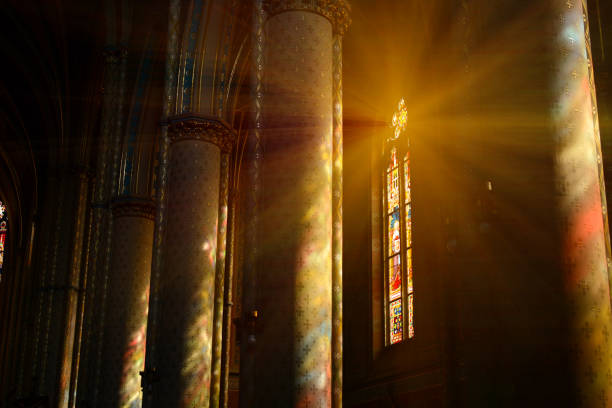 sunlight between the columns in catholic church - church stock photos and pictures