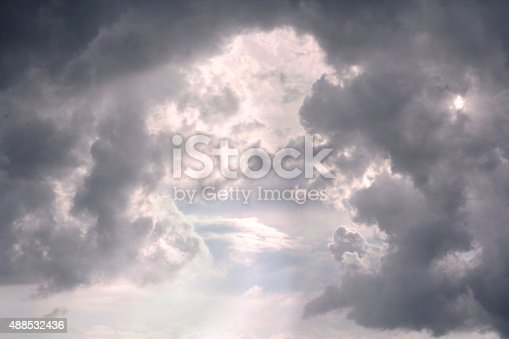 Bright sunlight is peeking between grey cumulonimbus clouds after a thunderstorm in the sky.