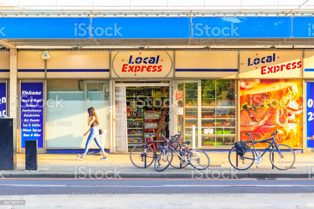 Sunlight casts a shadow on a grocery shop in Bermondsey, London with a female pedestrian passing by stock photo