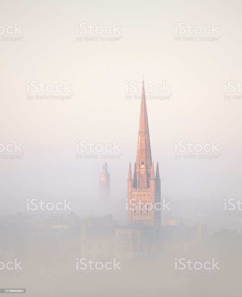 Sunlight catching the cathedral on a misty morning over Norwich city. stock photo
