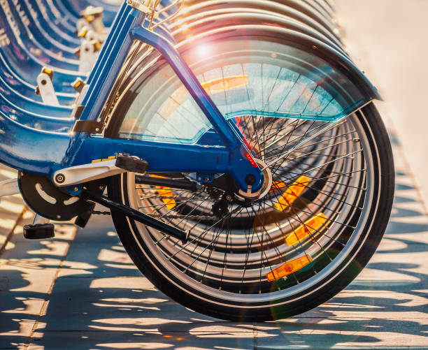 sunlight catching the rims of a row blue city bikes causing an attractive lens flare and shadows. Each bicycle has orange reflectors on the spokes and transparent  plastic mud guards stock photo