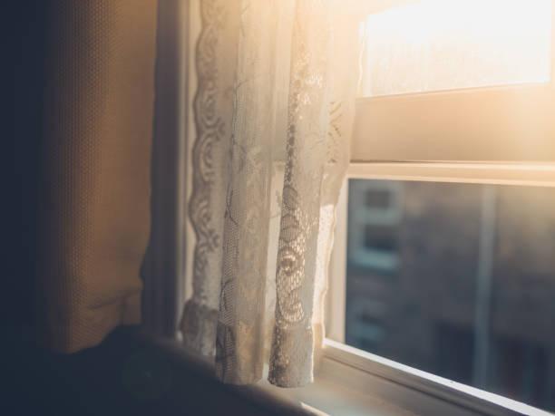 Sunlight hitting curtain by window stock photo