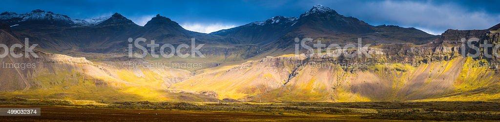 Sunlight illuminating dramatic mountain landscape snowy peaks Arctic pasture Iceland stock photo