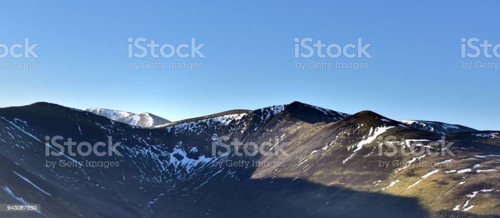 Sunlight on the snow on Grisedale Pike stock photo