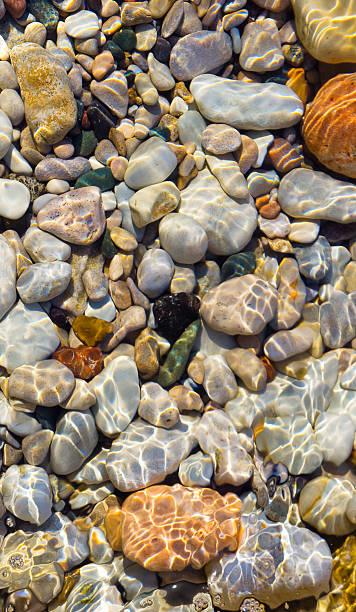 Sunlight on underwater pebbles stock photo