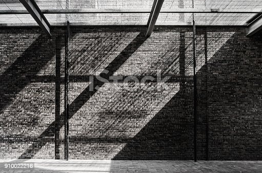 istock Sunlight pass through the net and reflecting on the brick wall and floor. 910022216