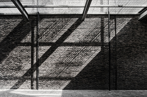 Sunlight pass through the net and reflecting on the brick wall and floor.
