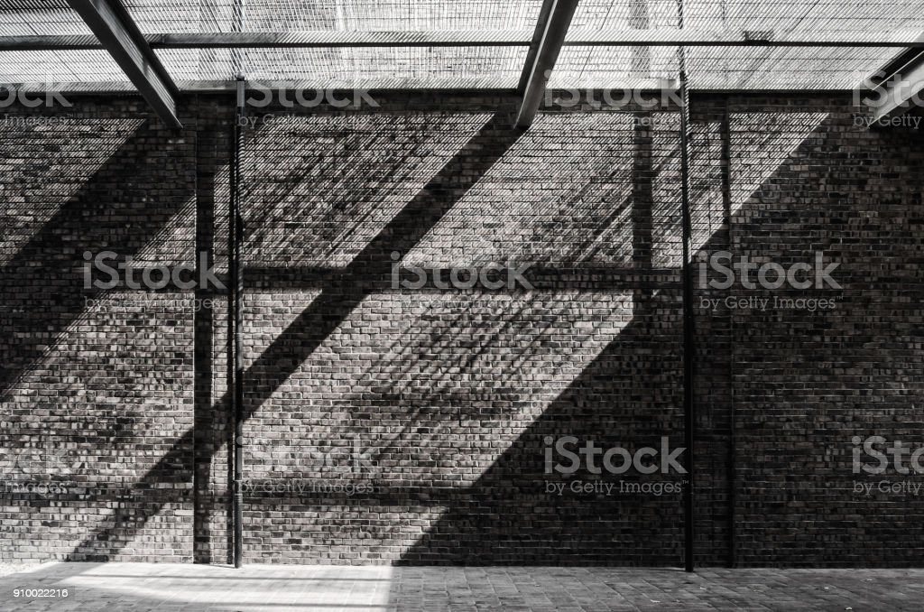 Sunlight pass through the net and reflecting on the brick wall and floor. stock photo