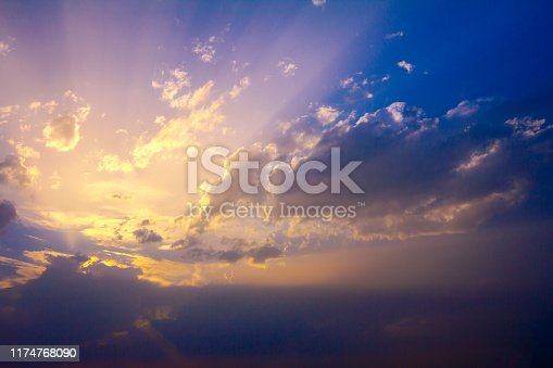 Scene of sunlight rays from cumulus clouds on the beautiful blue and purple sky.