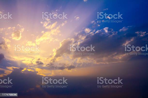 Photo of Sunlight rays from the clouds on a blue and purple sky
