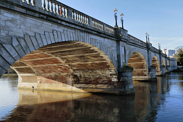 Five-span bridge across the River Thames at Kingston Sunlight reflecting off the River Thames onto the underside of the five arches that go to make up the river crossing bridge at Kingston-Upon-Thames in Surrey, England. whiteway stock pictures, royalty-free photos & images