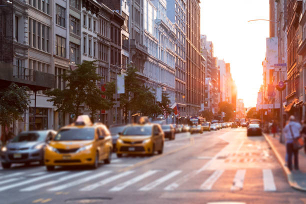 sunlight shines down the streets of new york city with taxis stopped at the intersection - wschód zdjęcia i obrazy z banku zdjęć