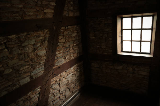 Sunlight shines into dark empty cellar through lonely window stock photo