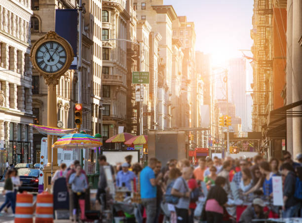 sonnenlicht scheint an den gebäuden von manhattan mit massen von menschen in new york city - uhrenshop stock-fotos und bilder