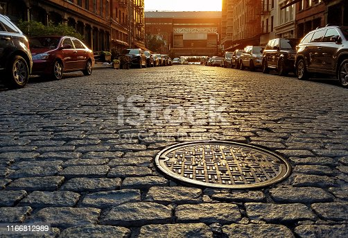 Sunlight shining on a cobblestone street and manhole cover in Manhattan New York City NYC