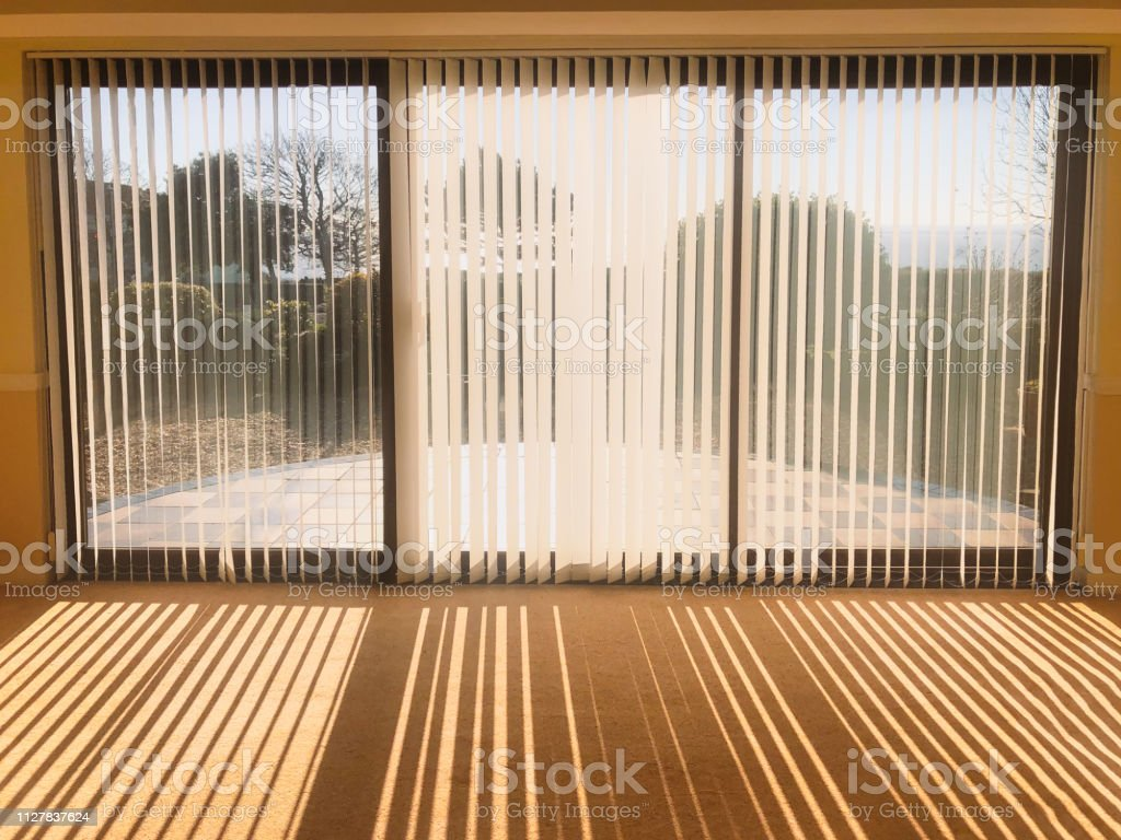 Sunlight Shining Through Full Length White Vertical Blinds In Front Of Three Glass Sliding French Doors Leading To A Patio Garden And Sea View Creating Shadow Stripes Stock Photo Download Image