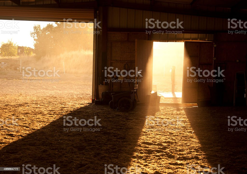 Sunlight shining through two barn doors at sunset with dust stock photo