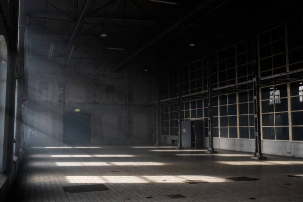 Sunlight shining throuh the windows of an old abandoned industrial warehouse building Sunlight shining throuh the windows of an old abandoned industrial warehouse building warehouse interior stock pictures, royalty-free photos & images
