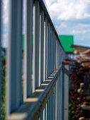 istock sunlight through a metal fence in summer 1077760698