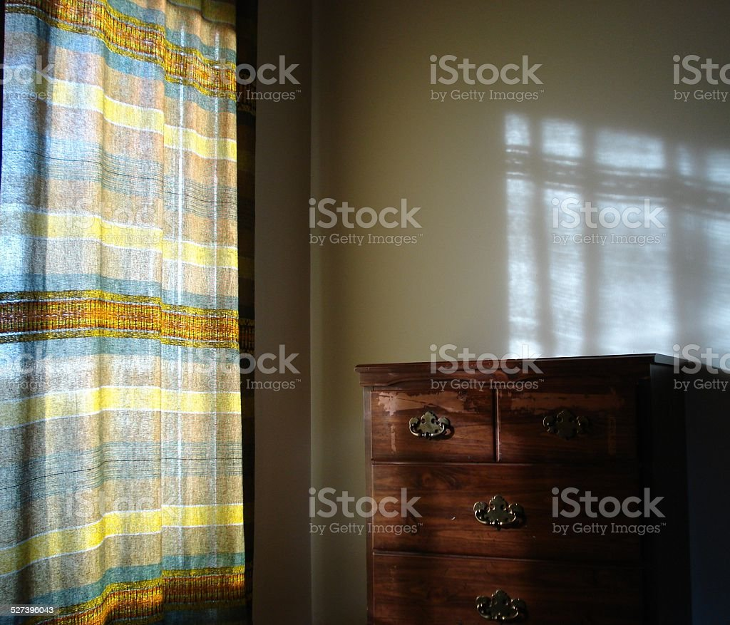 Sunlight through Curtains on Chest of Drawers stock photo
