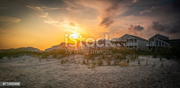 A brilliant sky hovers over beach homes nestled into the dunes.