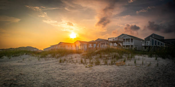 Sunlight Through the Dunes A brilliant sky hovers over beach homes nestled into the dunes. holiday villa stock pictures, royalty-free photos & images