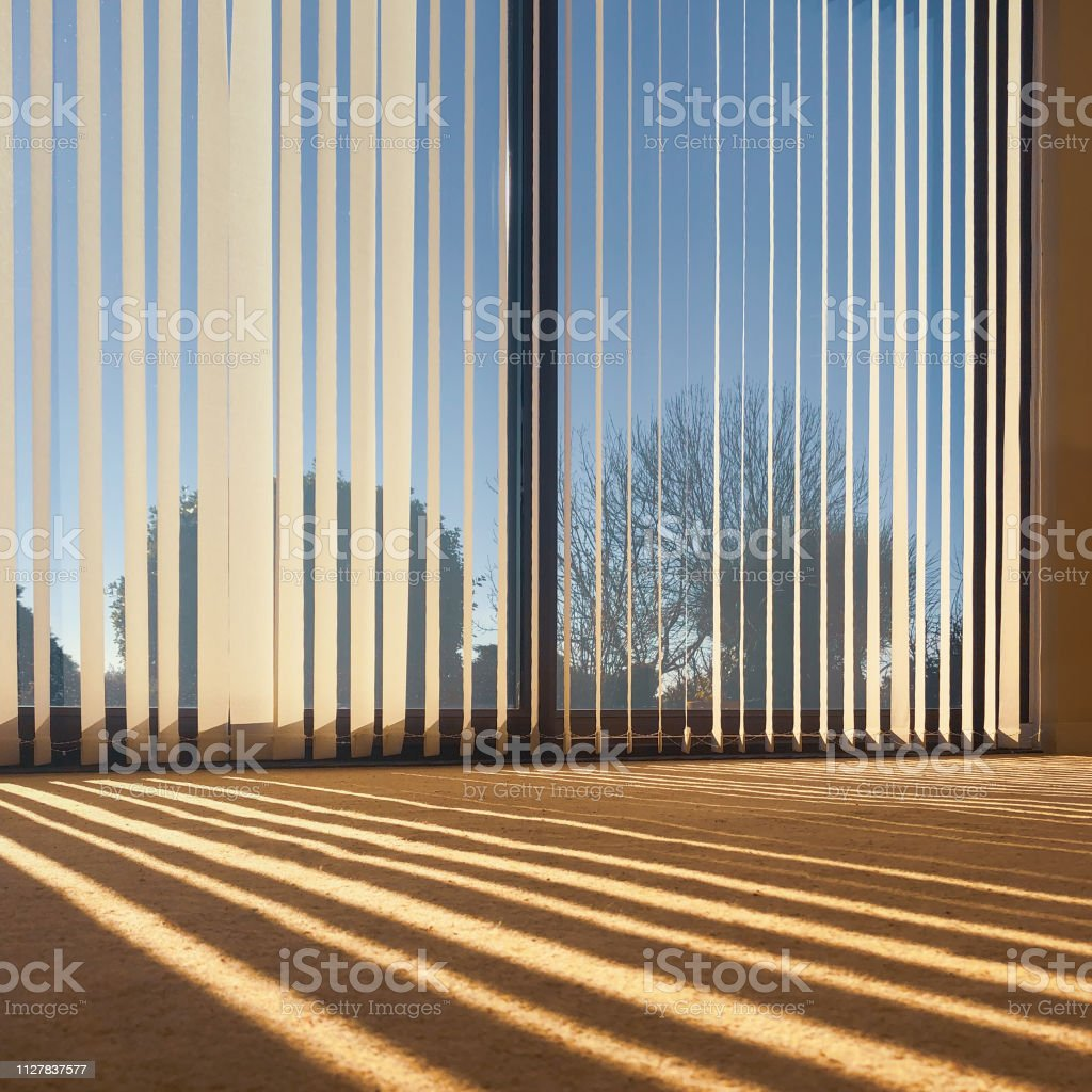 Sunlight Through Vertical Blinds Angled Slightly Open Hanging Over Large Sliding Interior Glass Doors And Throwing A Striped Shadow On To A Beige Carpet Stock Photo Download Image Now Istock