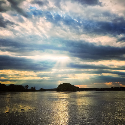 Beauitiful sunset sky over the water. Dramatic clouds and bright sunbeams.