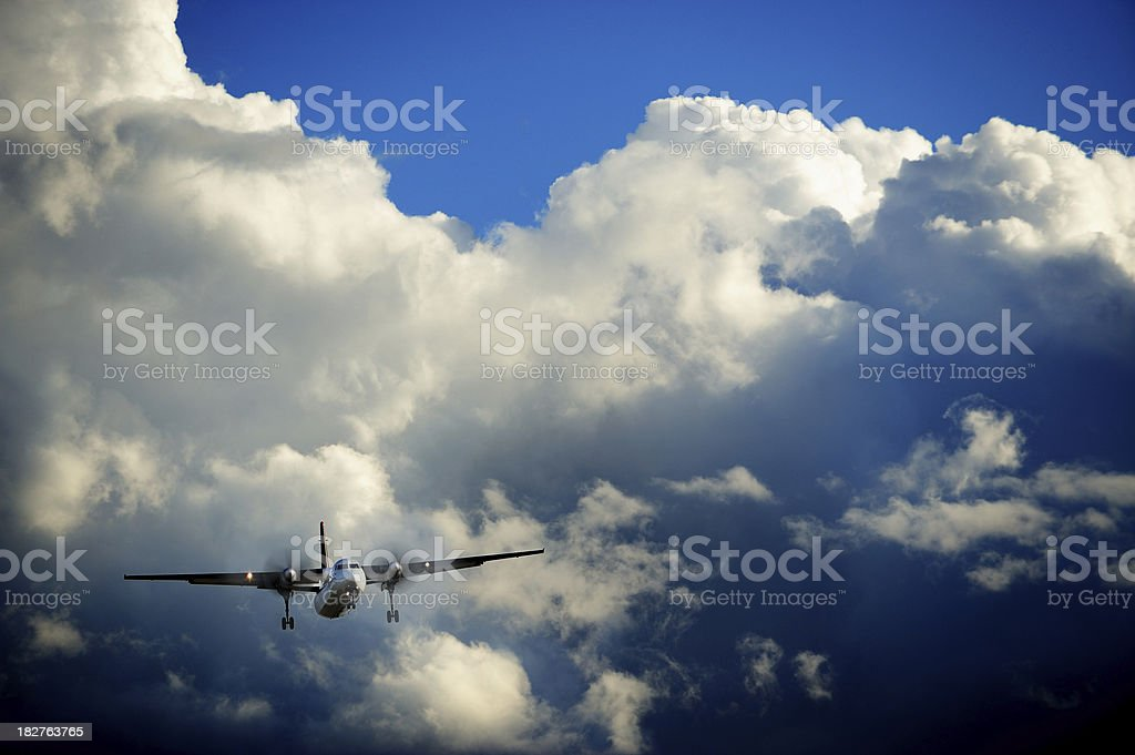 Sunlit airplane flying in bad weather royalty-free stock photo